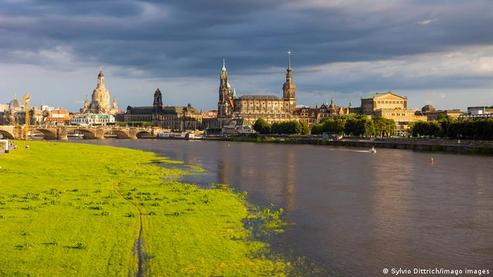 The skyline of Dresden along the Elbe River showing a green flood plain