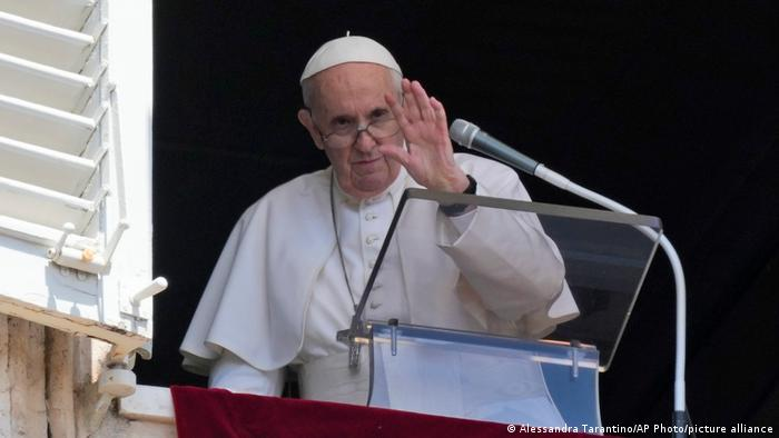 Pope Francis waves to the crowd after delivering the noon prayer