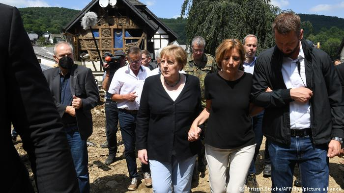 German Chancellor Angela Merkel (center) und Malu Dreyer (holding Merkel's hand) assess flood damage in Schuld, Germany