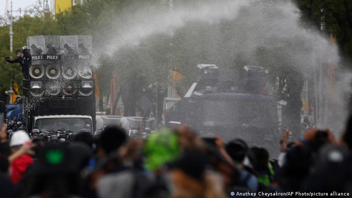 Police use water cannon to disperse protesters as they march to Government House in Bangkok