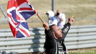 Lewis Hamilton waves a British flag