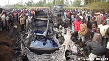 People stand next to a burnt out petrol tanker that burst into flames when it overturned in western Kenya, while a crowd thronged to collect the spilling fuel, some 315 kilometres (195 miles) northwest of Nairobi, on the busy highway between Kisumu and the border with Uganda, on July 18, 2021. - Thirteen people were killed and others seriously burned when a huge fireball engulfed a crowd in Kenya as they syphoned fuel from an overturned petrol truck that ignited without warning. Police said on July 18, 2021, the death toll could rise, with investigators trying to account for the missing, and charred bones found among the twisted wreckage of the fuel tanker. (Photo by - / AFP) (Photo by -/AFP via Getty Images)