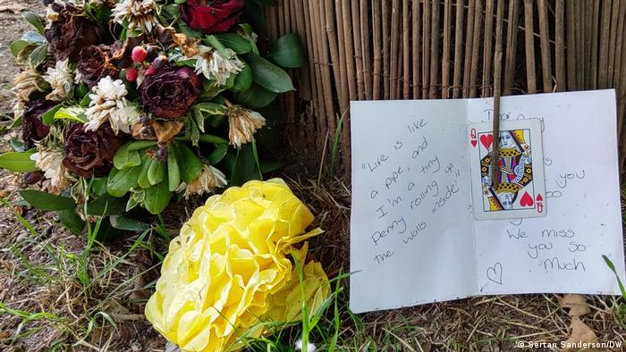 Flowers and card one the floor against a treet trunk across the road from Amy Winehouse' home