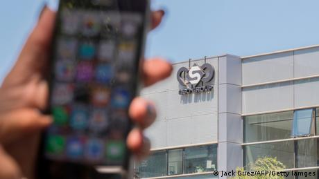 Foto de una mano que sostiene un smartphone frente a la sede del NSO Group