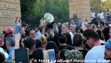 18.06.2021 A Greek Orthodox priest speaks to demonstrators during a protest against government safety measures during the coronavirus pandemic, outside the presidential palace in Nicosia, Cyprus, Monday, July 18, 2021. (AP Photo/Petros Karadjias)