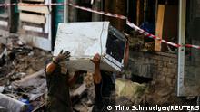 Men carry an electronic equipment as they clean rubble in an area affected by floods caused by heavy rainfalls in Bad Muenstereifel, Germany, July 18, 2021. REUTERS/Thilo Schmuelgen