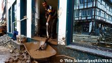 Ein Helfer entfernt Schlamm mit einer Schaufel aus einem Gebäude in eine Schubkarre, die vorne außerhalb des Gebäudes steht.