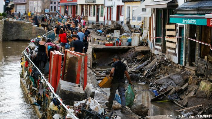 Police officers and volunteers clean rubble in an area affected by floods