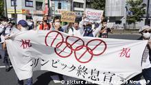 Demonstranten marschieren mit einem Banner und Plakaten bei einem Protest gegen die Olympischen und Paralympischen Sommerspiele. +++ dpa-Bildfunk +++