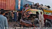 19.07.21 *** In this handout photo released by Punjab Province's Emergency Service Rescue 11222, shows residents and rescue workers at the site of a deadly bus accident near Dera Ghazi Khan, Pakistan, Monday, July 19, 2021. The speeding bus carrying mostly laborers traveling home for a major Muslim holiday rammed into a container truck on a busy highway in central Pakistan, killing and injuring dozens, police and rescue officials said. (Emergency Service Rescue 1122 via AP)