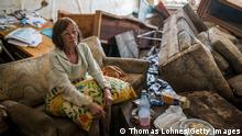 BAD NEUENAHR, GERMANY - JULY 17: Jutta Schnelleckes (72) sits in the living room of her apartment, which was completely destroyed by the flood on July 17, 2021 in Bad Neuenahr, Germany. The furniture has been overturned. Electricity and water do not work. She has been living in the mess for 2 days. Her husband sits in the bedroom with the dog with an injured foot. A neighbor helps shovel out mud. Firefighters will later escort her out of her apartment and find shelter. While the water masses are slowly receding from many flooded areas in North Rhine-Westphalia and Rhineland-Palatinate, the search for fatalities continues in the rubble of the disaster areas. By Saturday, that number had risen to more than 130, with more than 90 people killed in the greater Ahrweiler area alone, according to police. (Photo by Thomas Lohnes/Getty Images)