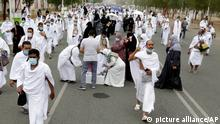 Muslim pilgrims receive free water as they walk to the Namira Mosque in Arafat during the annual hajj pilgrimage, near the holy city of Mecca, Saudi Arabia, Monday, July 19, 2021. Tens of thousands of vaccinated Muslim pilgrims circled Islam's holiest site in Mecca on Sunday, but remained socially distanced and wore masks as the coronavirus takes its toll on the hajj for a second year running. What once drew some 2.5 million Muslims from all walks of life from across the globe, the hajj pilgrimage is now almost unrecognizable in scale. (AP Photo/Amr Nabil)