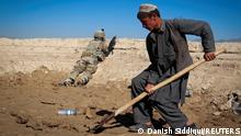 FILE PHOTO: An Afghan boy works at a construction site as a U.S. Army soldier of 3/1 AD Task Force Bulldog takes position during a joint patrol with Afghan National Army (ANA) in a village in Kherwar district in Logar province, eastern Afghanistan, May 23, 2012. REUTERS/Danish Siddiqui/File Photo