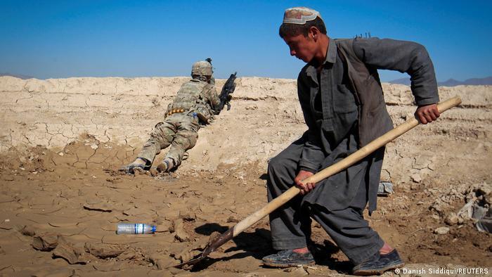 Afghanistan | Ein Junge arbeitet im Hintergrund ein US Army Sodat