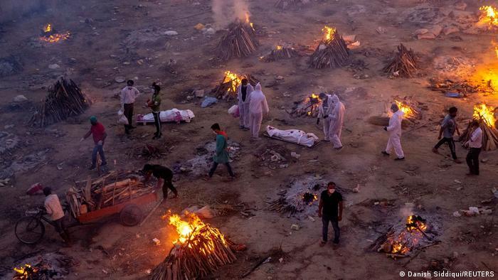 Foto mostra fogueiras onde corpos estão sendo queimados. Há algumas pessoas com roupa de proteção. Outras vestem roupas normais.