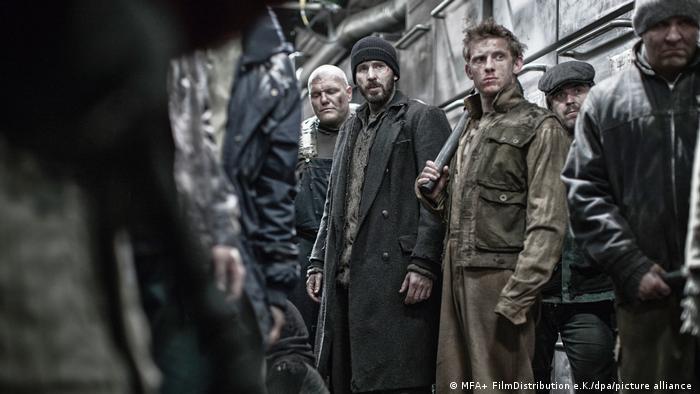 In einer Szene des Films Snowpiercer stehen Männer mit dreckigen Gesichtern in einem Zug