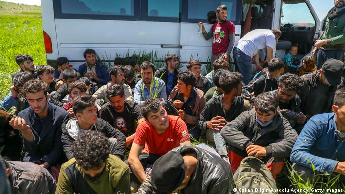 Illegal immigrants sit on the ground outside of a van involved in an accident
