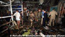 BAGDAD, IRAQ - JULY 19: Iraqi security forces and citizens inspect the site after a blast at Al-Wahilat market in Sadr district of Baghdad, Iraq on July 19, 2021. It is reported that 22 were killed and 47 injured. Murtadha Al-Sudani / Anadolu Agency