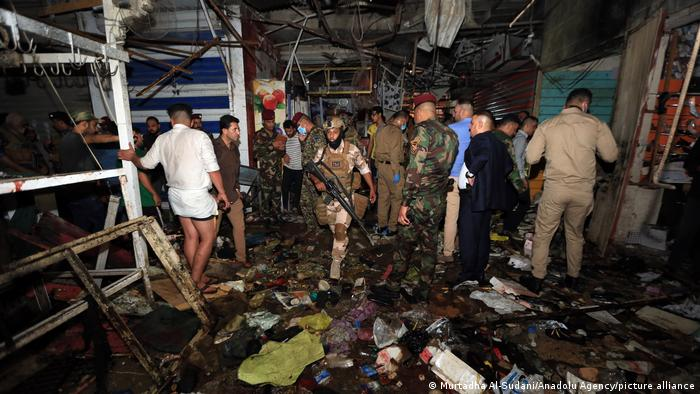 Iraqi soldiers and civilians inspecting the site of the bombing at the al-Wahilat market in the Sadr district of Baghdad. There is blackened debris all over the floor. Lots of men are standing around while an armed soldier walks towards the camera.