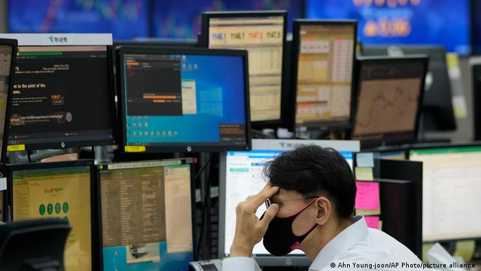 A currency trader watches monitors at the foreign exchange dealing room of the KEB Hana Bank headquarters in Seoul, South Korea