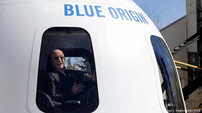 Amazon and Blue origin founder Jeff Bezos speaks from a New Shepard mockup  - 58323162 401 - Amazon′s Bezos returns to Earth after first space flight | News | DW