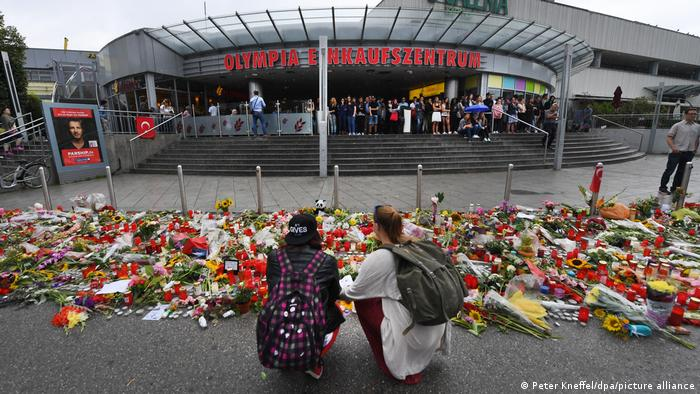 Two people crouch down before flowers left for the victims of the 2016 Munich shooting