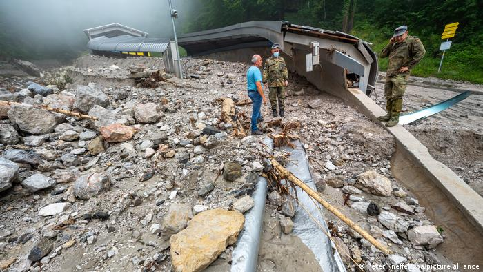 A resident and two German soldiers survey storm damage at the Königssee bobsleigh, luge, and skeleton track