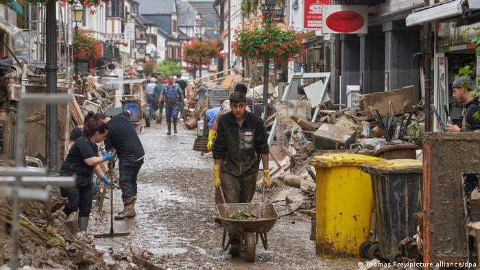 People cleaning the streets of mud and rubble