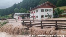 Wasser fließt über einen Platz vor einem Haus. Der Landkreis Berchtesgadener Land hat nach starkem Regen wegen Hochwassers den Katastrophenfall ausgerufen. +++ dpa-Bildfunk +++