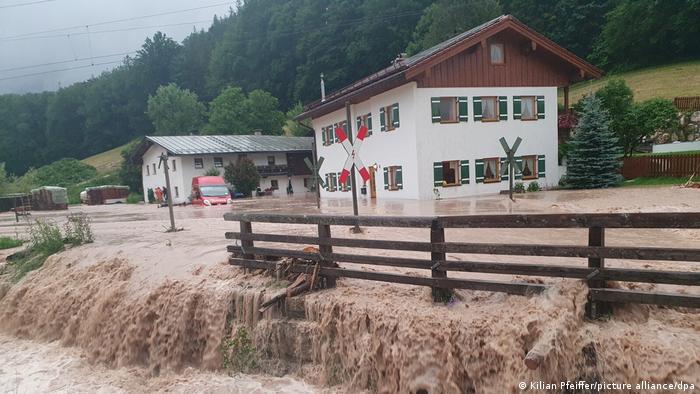 Zwei Häuser mit Holzläden stehen am Hang im Hochwasser an einer Straße, von der braunes Wasser herunterströmt