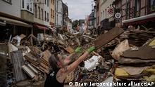 A woman throws away rubbish in the centre of Bad Neuenahr-Ahrweiler, Germany, Monday July 19, 2021. More than 180 people died when heavy rainfall turned tiny streams into raging torrents across parts of western Germany and Belgium, and officials put the death toll in Ahrweiler county alone at 110. (AP Photo/Bram Janssen)