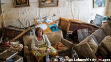 Germany Continues Evacuation And Rescue From Floods As Death Toll Rises BAD NEUENAHR, GERMANY - JULY 17: Jutta Schelleckes (72) sits in the living room of her apartment, which was completely destroyed by the flood on July 17, 2021 in Bad Neuenahr, Germany. The furniture has been overturned. Electricity and water do not work. She has been living in the mess for 2 days. Her husband sits in the bedroom with the dog with an injured foot. A neighbor helps shovel out mud. Firefighters will later escort her out of her apartment and find shelter. While the water masses are slowly receding from many flooded areas in North Rhine-Westphalia and Rhineland-Palatinate, the search for fatalities continues in the rubble of the disaster areas. By Saturday, that number had risen to more than 130, with more than 90 people killed in the greater Ahrweiler area alone, according to police. (Photo by Thomas Lohnes/Getty Images)