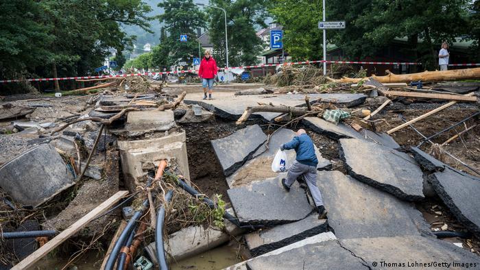 A man climbs over a destroyed bridge
