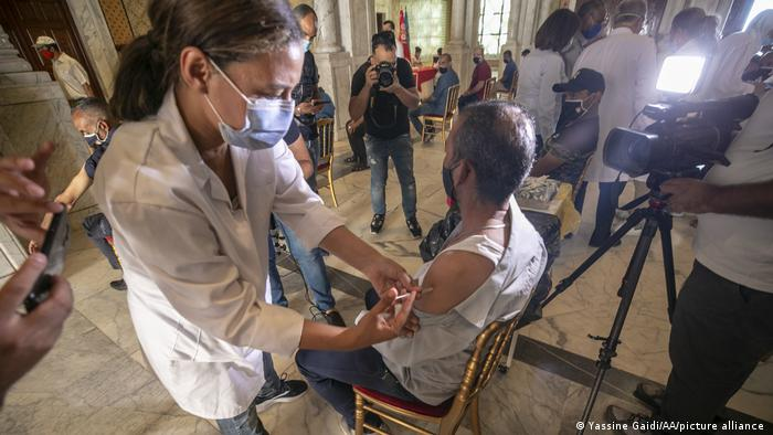 A woman vaccinates a seated man, photographers take pictures