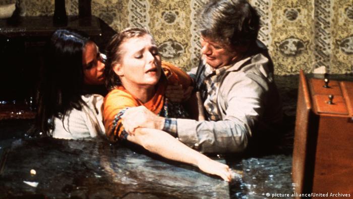 Filmstill aus Flood: In einer Wohnung stehen drei Menschen bis zur Brust im Wasser