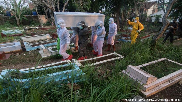 Health workers in personal protective equipment carry a coffin of a COVID-19 victim in Jakarata, Indonesia