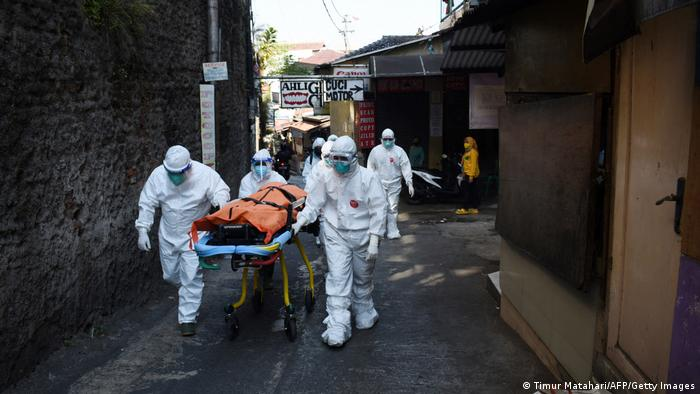 Health workers remove the body of a COVID victim, who died while isolating at home in Bandung, Indonesia