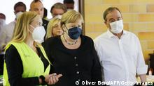 German Chancellor Angela Merkel (C) and North Rhine-Westphalia's State Premier, Christian Democratic Union (CDU) leader and CDU's candidate for Chancellery Armin Laschet (R) arrive to visit a food relief center in the flood-ravaged spa town Bad Munstereifel, North Rhine-Westphalia state, western Germany, on July 20, 2021. - The German government on July 19, 2021 pledged to improve the country's under-fire warning systems as emergency services continued to search for victims of the worst flooding in living memory, with at least 165 people confirmed dead. (Photo by Oliver Berg / POOL / AFP) (Photo by OLIVER BERG/POOL/AFP via Getty Images)