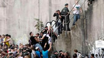 Love Parade visitors attempt to reach a staircase to escape the crowd