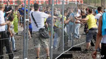 Festival-goers attempt to separate sections of fence to get out of the Love Parade grounds