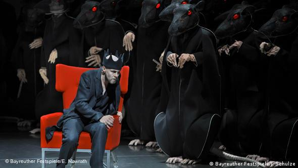 Actors in rat costumes surround a seated actor in Lohengrin