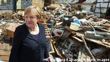 German Chancellor Angela Merkel walks pas debris as she visits the flood-ravaged city of Iversheim, near Bad Munstereifel, North Rhine-Westphalia state, western Germany, on July 20, 2021. - The German government on July 19, 2021 pledged to improve the country's under-fire warning systems as emergency services continued to search for victims of the worst flooding in living memory, with at least 165 people confirmed dead. (Photo by WOLFGANG RATTAY / POOL / AFP) (Photo by WOLFGANG RATTAY/POOL/AFP via Getty Images)