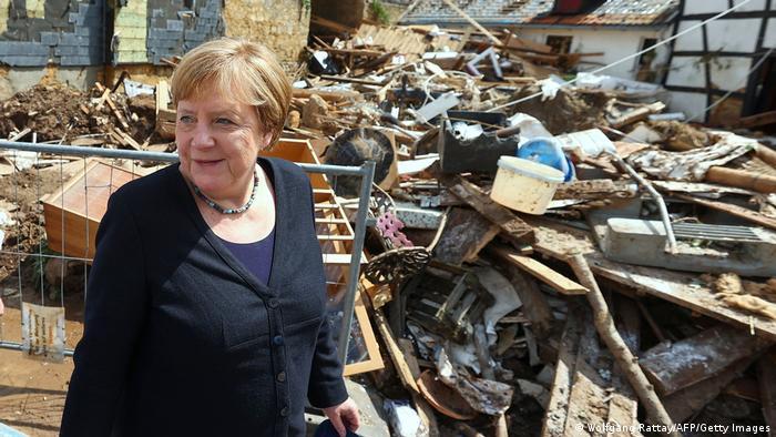 Merkel standing next to a pile of debris