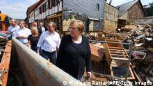 Ангела Меркель рассматривает разрушения, оставленные стихией в Бад-Мюнстерайфеле