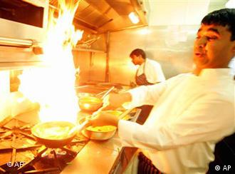 A chef in the Deyna restaurant in London stands back as he cooks a hot Indian dish