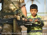 Criança segura metralhadora de soldado inglês, no Iraque