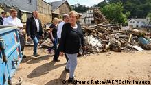 German Chancellor Angela Merkel (R) and North Rhine-Westphalia's State Premier, Christian Democratic Union (CDU) leader and CDU's candidate for Chancellery Armin Laschet (2ndR) visit the flood-ravaged city of Iversheim, near Bad Munstereifel, North Rhine-Westphalia state, western Germany, on July 20, 2021. - The German government on July 19, 2021 pledged to improve the country's under-fire warning systems as emergency services continued to search for victims of the worst flooding in living memory, with at least 165 people confirmed dead. (Photo by WOLFGANG RATTAY / POOL / AFP) (Photo by WOLFGANG RATTAY/POOL/AFP via Getty Images)