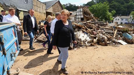 German Chancellor Angela Merkel (R) and North Rhine-Westphalia's State Premier, Christian Democratic Union (CDU) leader and CDU's candidate for Chancellery Armin Laschet (2ndR) visit the flood-ravaged city of Iversheim, near Bad Munstereifel,