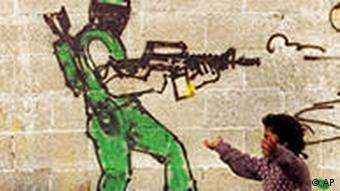 A Palestinian boy walks past a drawing of a masked man shooting a gun