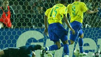 Brazil's Ronaldo, right, runs away after slotting the ball past Germany's Oliver Kahn, right, to score the opening goal during the 2002 World Cup final